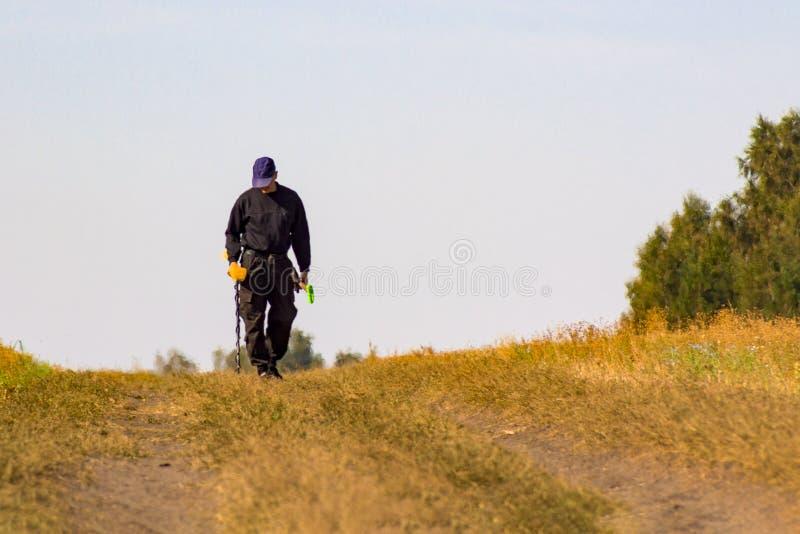 Человек при электронный прибор металлоискателя работая на предпосылке outdoors Фотография конца-вверх искать процесс стоковое изображение rf