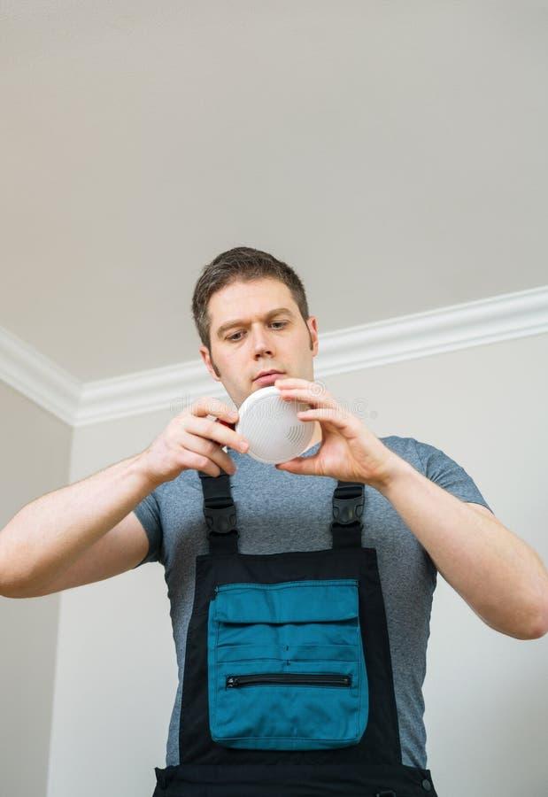 Человек проверяя батарею в индикаторе дыма стоковые изображения rf