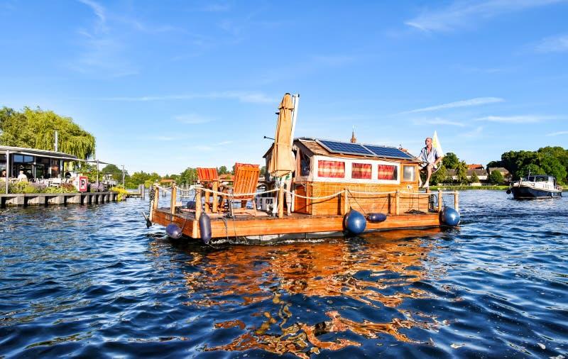 Человек проводит плавучий дом через Malchower видит в Германии стоковые фотографии rf