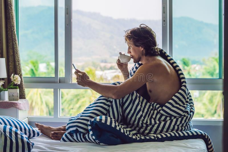 Человек проспал вверх в утре и читает новости на таблетке на заднем плане окна с целью гор стоковое изображение rf