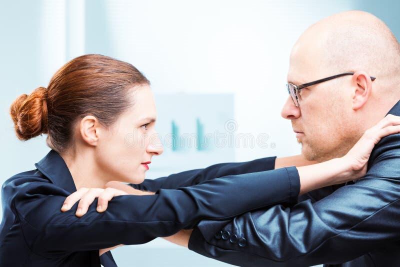 Человек против офиса женщины воюя в офисе стоковое изображение