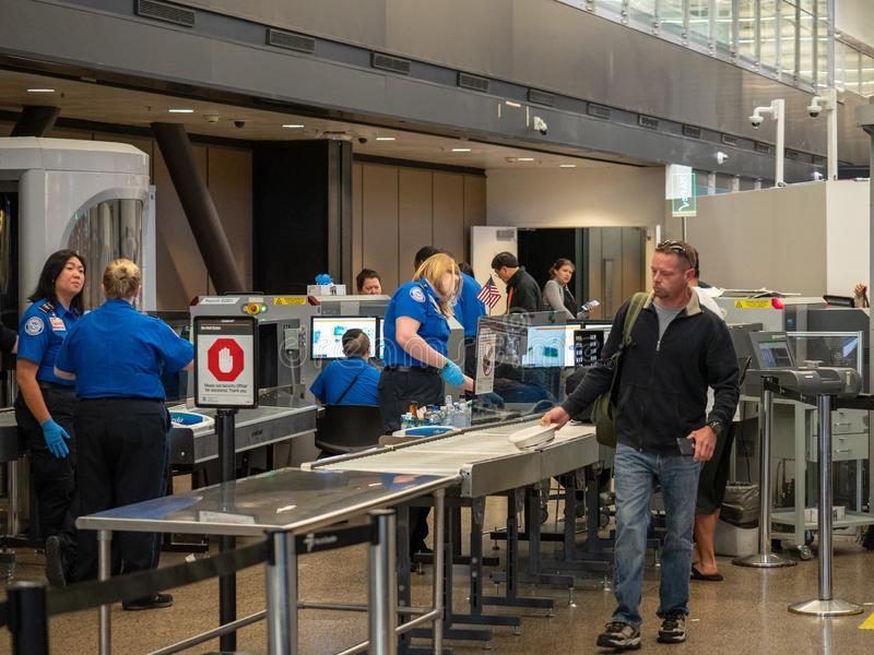 Человек проходит хотя контрольно-пропускной пункт безопасностью администрации TSA безопасностью транспорта на международный аэроп стоковые фотографии rf