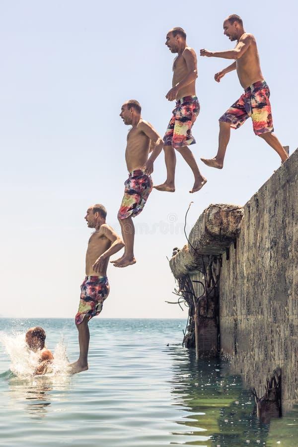 Человек прыгает с пирса стоковое фото rf