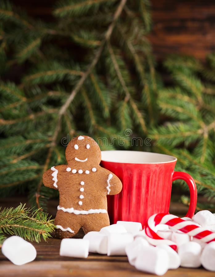 Человек пряника около больших красных чашки и тросточки рождественской елки, рождества и зефира стоковая фотография rf
