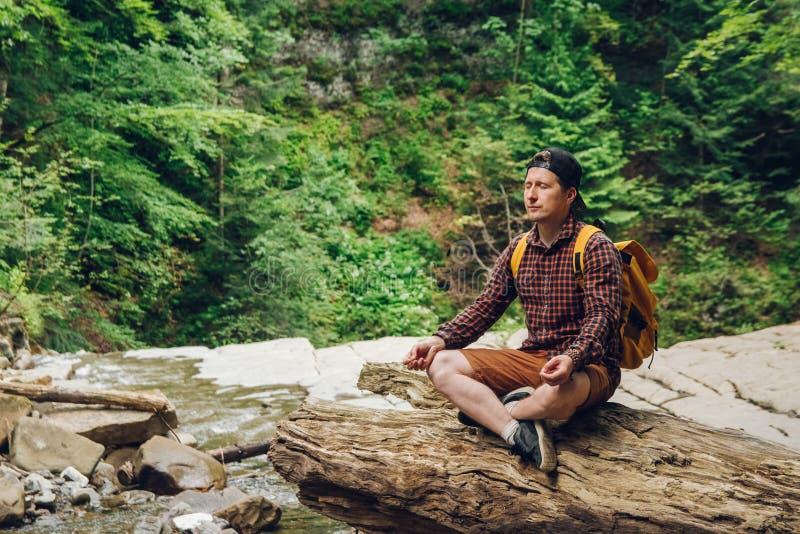 Человек путешественника в медитативном положении с рюкзаком сидя на стволе дерева на фоне леса и стоковое фото rf