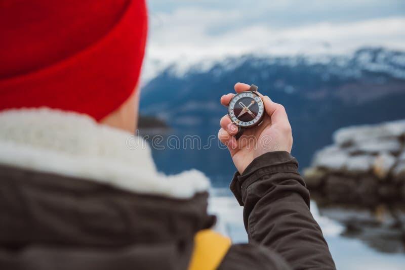 Человек путешественника держит старый компас на фоне горы и озера Концепция считать стоковая фотография rf