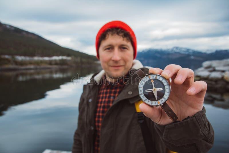 Человек путешественника держит старый компас на фоне горы и озера Концепция считать стоковые фотографии rf