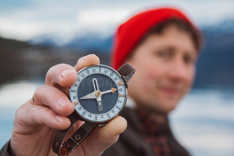 Человек путешественника держит старый компас на фоне горы и озера Концепция считать стоковое изображение