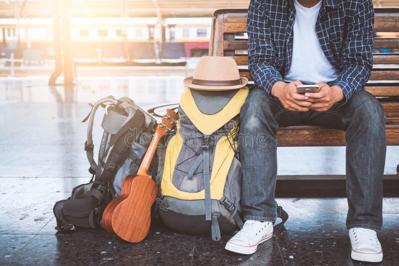 Человек путешественника используя смартфон для планировать отключение в вокзале Бангкока стоковые изображения rf