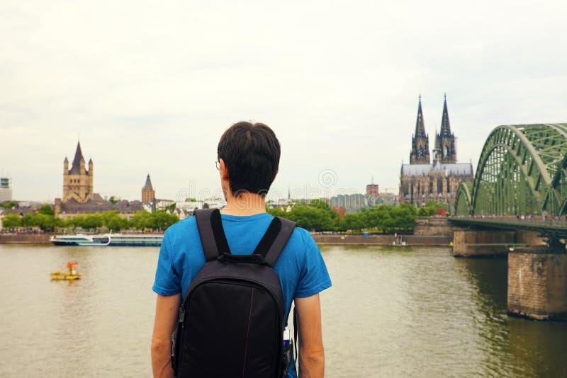 Человек путешественника наслаждаясь его праздником в Европе Вид сзади мужского backpacker смотря к городу Кёльна с собором и мост стоковое фото