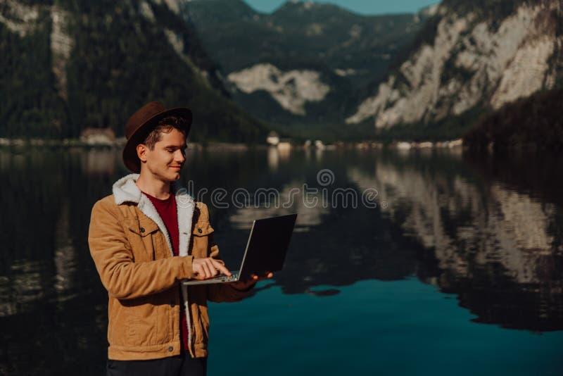 Человек путешественника ослабляя на шлюпке используя ноутбук в изумляя острове горы утеса ландшафта природы на предпосылке озера стоковое изображение rf