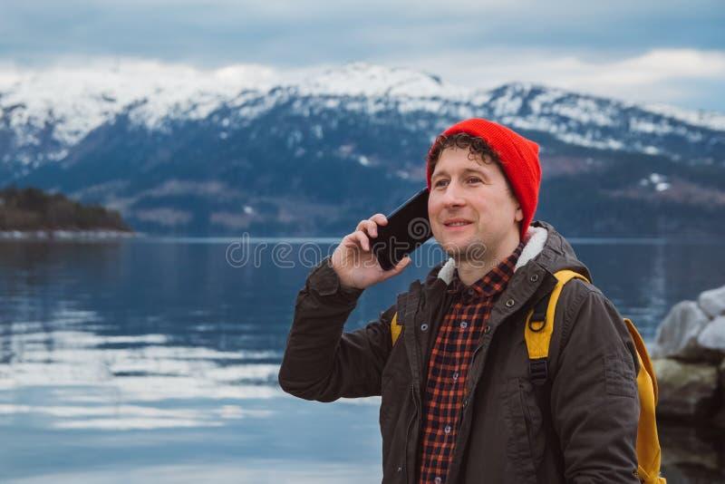 Человек путешественника портрета говоря на мобильном телефоне Турист в желтом рюкзаке стоя на предпосылке горы и стоковое изображение rf