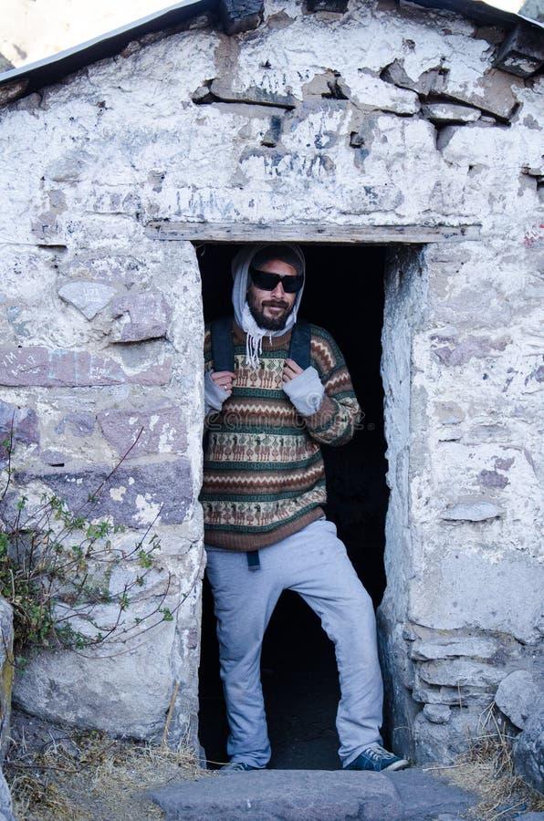 Человек путешественника при стекла представляя на доме ` s Даниеля Russo в Marcahuasi стоковое фото rf