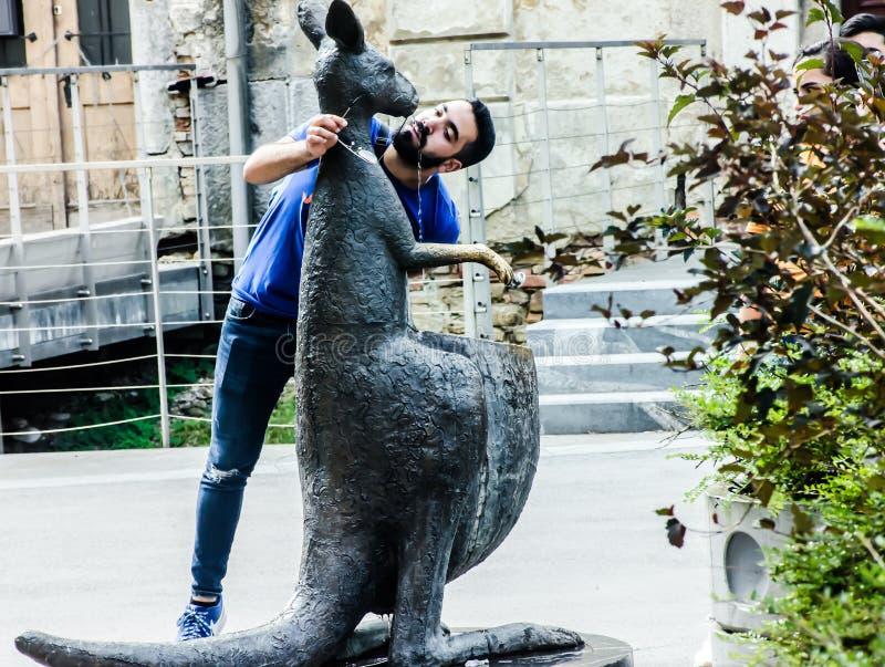 Человек пьет воду из фонтана кенгуру в Любляне, Словения стоковое фото