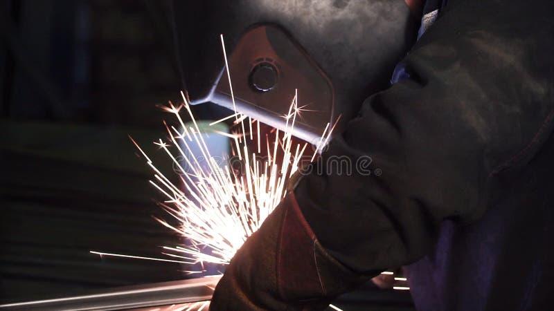Человек работает с сварочным аппаратом зажим Сваривая стальные структуры в фабрике Красивые искры летают вне стоковое фото rf