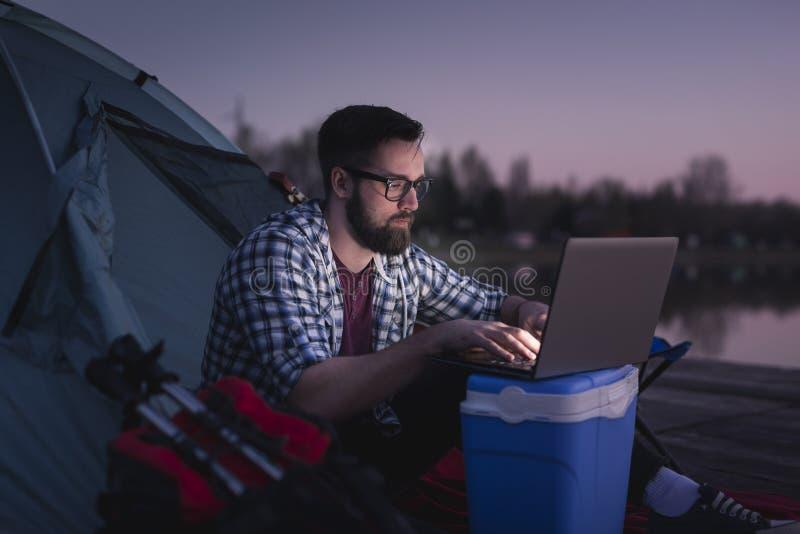 Человек работая на ноутбуке пока располагающся лагерем стоковые фото