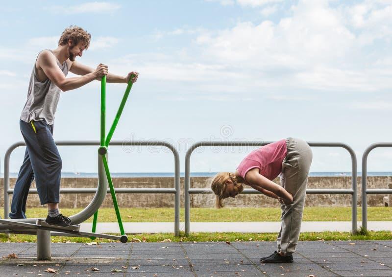 Человек работая на эллиптических тренере и женщине стоковое изображение