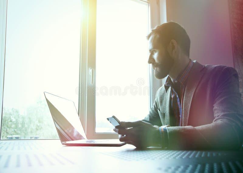 Человек работая с компьтер-книжкой и телефоном стоковая фотография rf