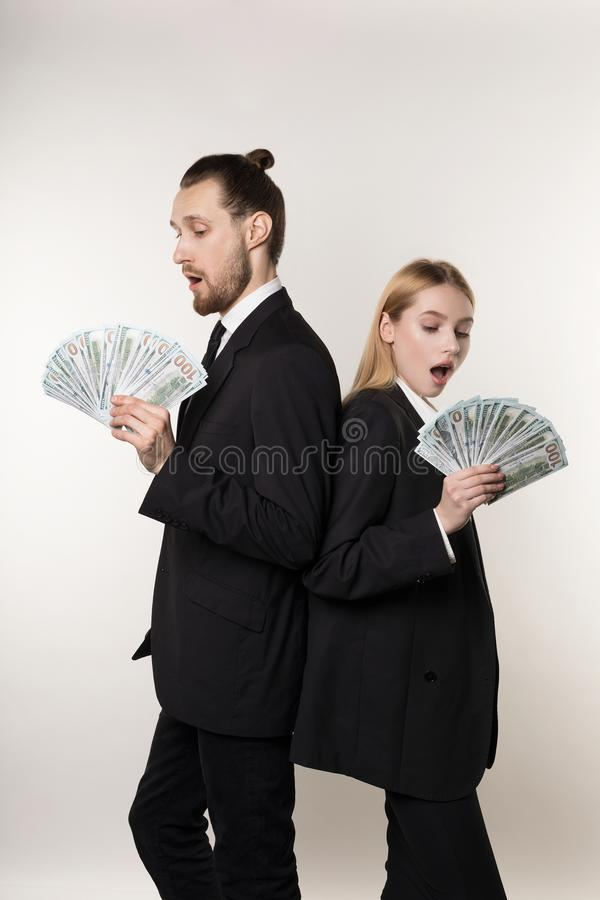 Человек 2 работников красивый и красивая белокурая женщина в черных костюмах стоя спина к спине с деньгами в руках стоковое изображение rf