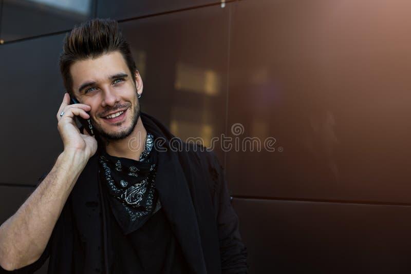 Человек радостной бороды стильный зноня по телефону через смартфон стоковое фото rf