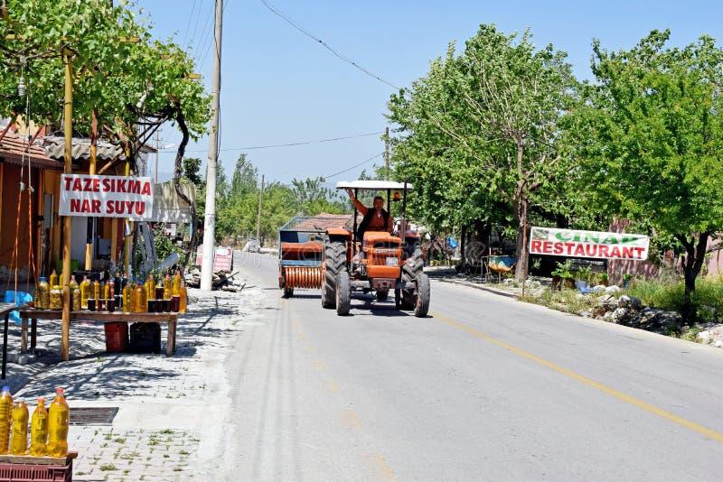 Человек развевая по мере того как он управляет красным трактором вниз с дороги стоковое изображение