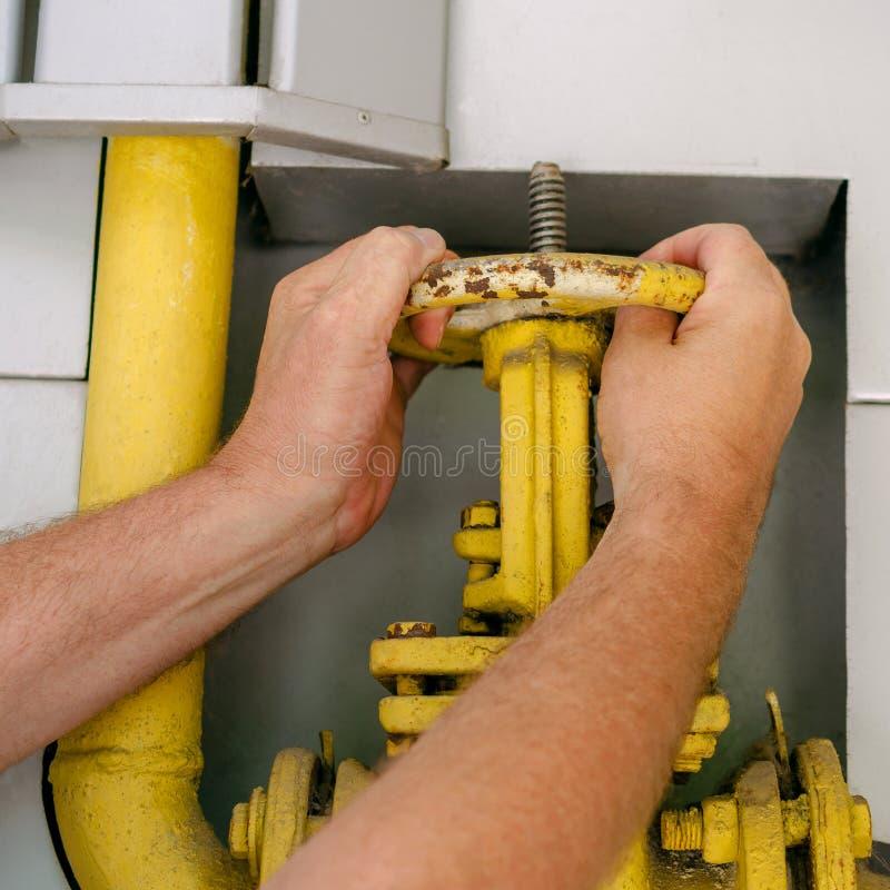 Человек раскрывает или закрывает на клапане трубы газа для того чтобы контролировать enterin газов стоковые фото