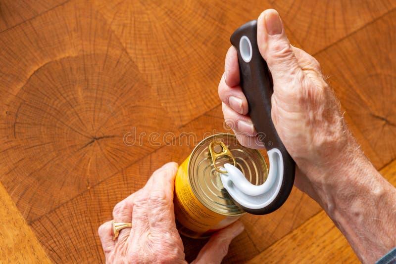 Человек раскрывая жестяную коробку с особенным консервооткрывателем стоковые фотографии rf