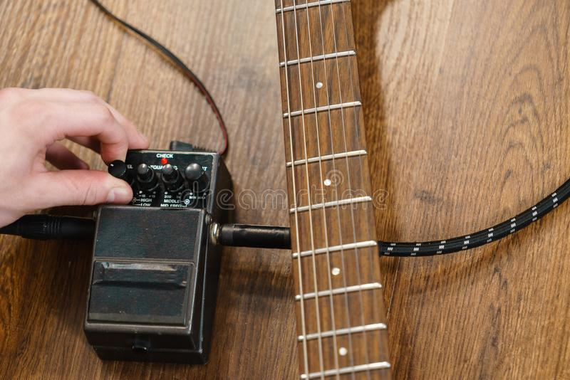 Человек регулируя гитару производит эффект педаль стоковое фото rf