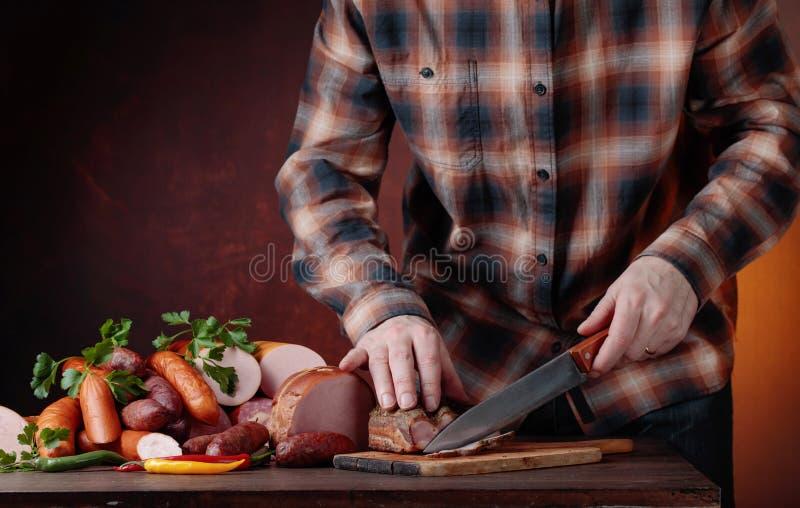 Человек режет различные сосиски и копченое мясо стоковые изображения