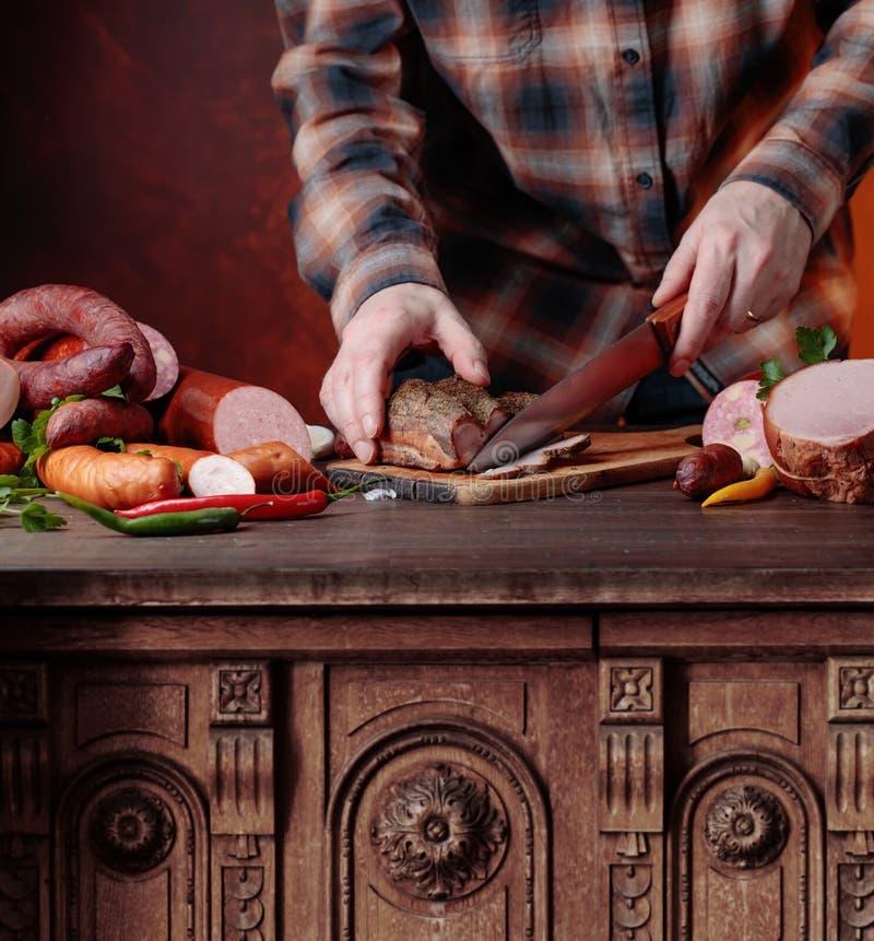 Человек режет различные сосиски и копченое мясо стоковые изображения rf