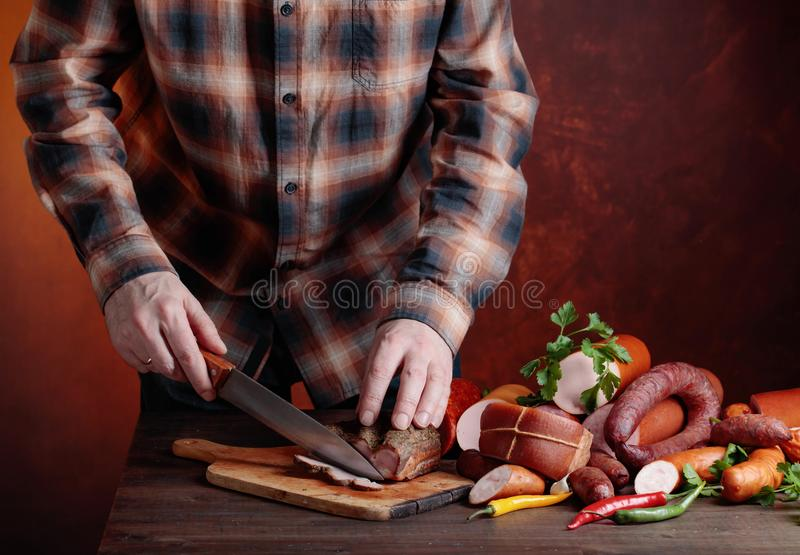 Человек режет различные сосиски и копченое мясо стоковое изображение