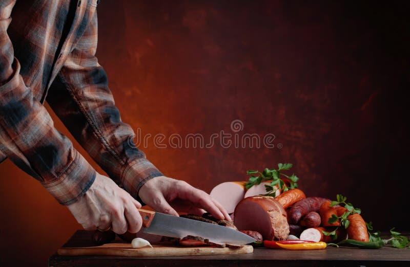 Человек режет различные сосиски и копченое мясо стоковое фото rf