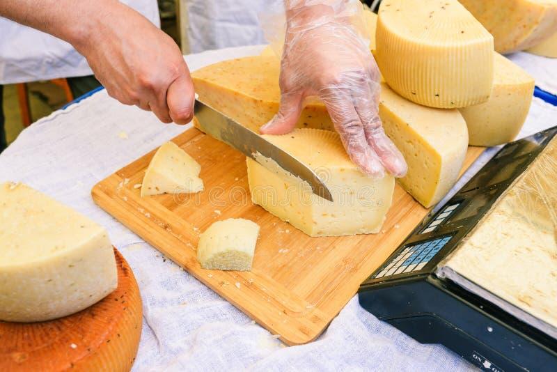 Человек режет сыр для продажи и дегустацию Деревянная доска и белая скатерть на которой лежат головы свежего сыра Конец-вверх  стоковая фотография rf