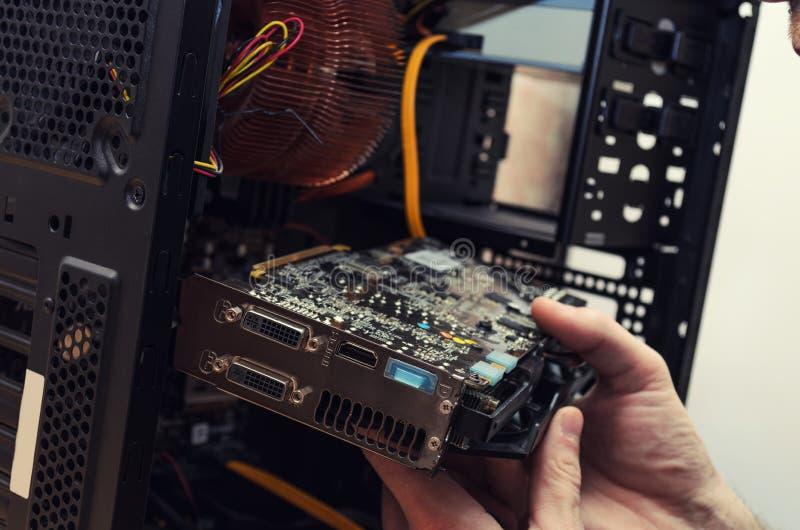 Человек ремонтирует компьютер, заменяя видеокарту стоковое фото rf