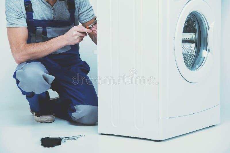 Человек ремонтирует стиральную машину стоковое фото rf