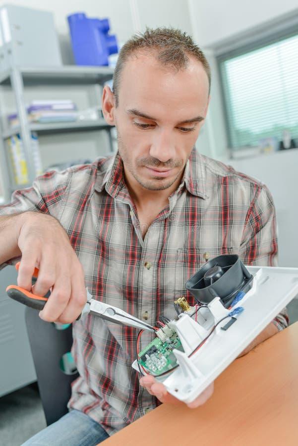 Человек ремонтируя охлаждающий вентилятор стоковое фото