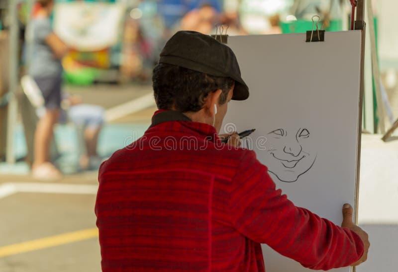 Человек рисует портрет на белой бумаге на улице стоковые фотографии rf