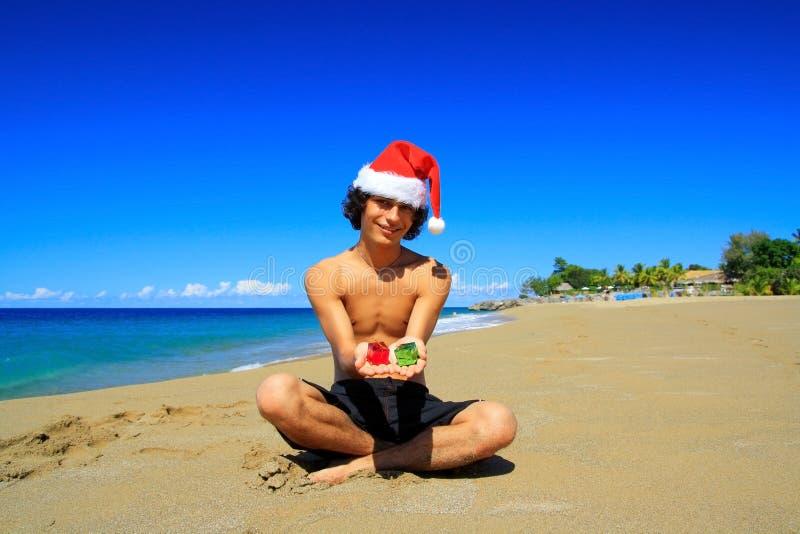Человек Санта с настоящими моментами на карибском пляже стоковое изображение