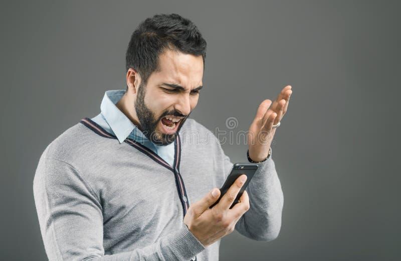 Человек сердитый с телефоном стоковое изображение rf