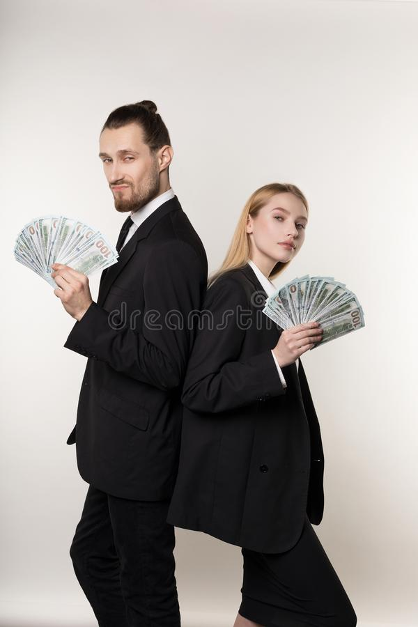 Человек 2 серьезных деловых партнеров красивый бородатый и красивая белокурая девушка стоя спина к спине с деньгами в руках стоковое изображение