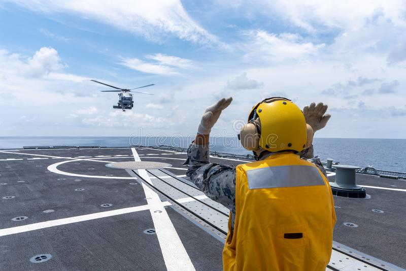Человек сигнала дает сигнал рукой вертолету Sikorsky MH-60S Seahawk приземлиться на кабину экипажа HTMS Bhumibol Adulyadej стоковые изображения rf