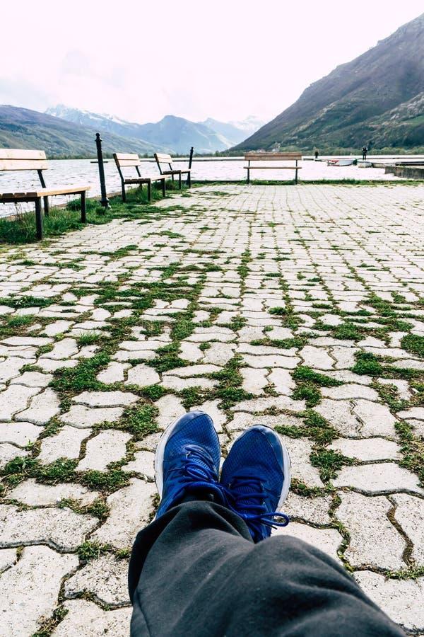 Человек сидит на деревянной скамье на озере горы трава в мостовой, горах на горизонте и долине Ноги в ботинках спорта стоковое фото rf