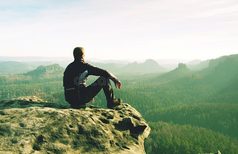 Человек сидит на крае скалы против предпосылки тумана стоковые изображения rf