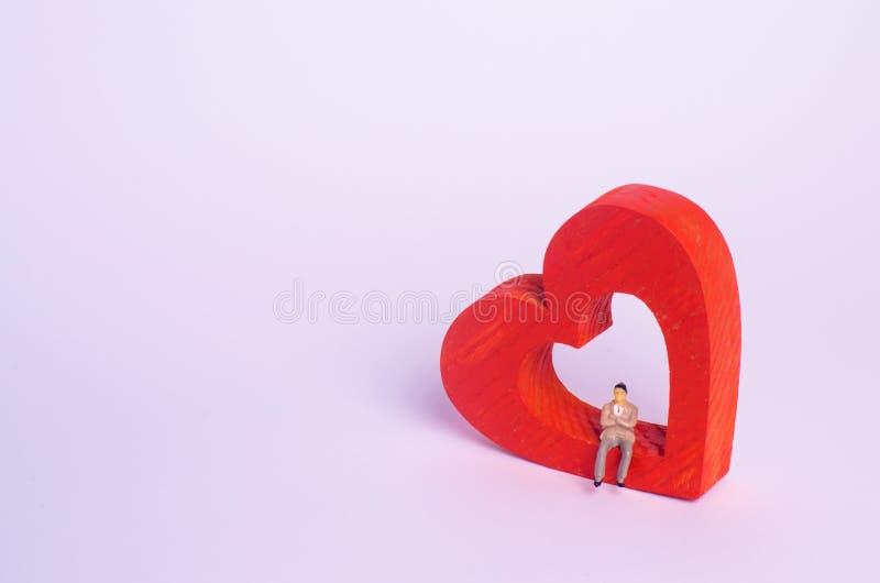 Человек сидит на красном сердце и ждет Сиротливая персона ищет ответная часть души, партнер Место для датировать Концепция влюбле стоковое фото rf