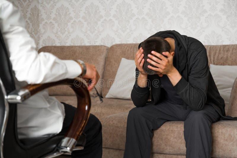 Человек сидит на кресле и говорит к психологу пока доктор делает примечания стоковые изображения