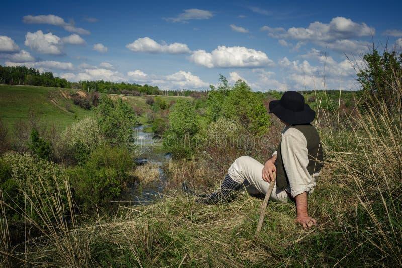 Человек сидит на холме около реки стоковое изображение rf