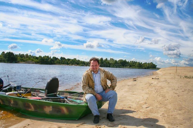 Человек сидит на шлюпке с рыболовными снастями на пляже реки стоковая фотография