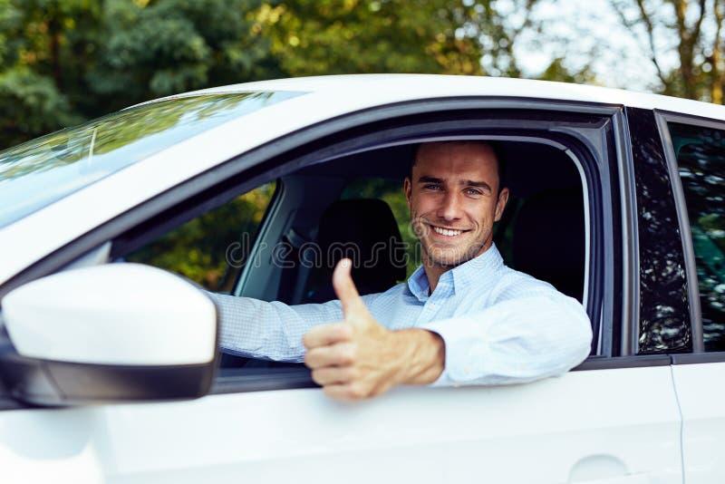 Человек сидя в автомобиле показывая большой палец руки вверх стоковые фотографии rf