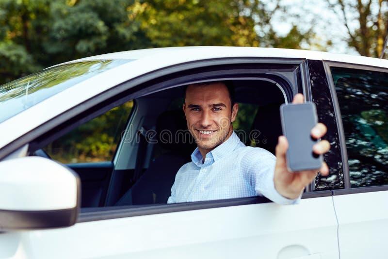 Человек сидя в его автомобиле и держа сотовый телефон стоковые фотографии rf