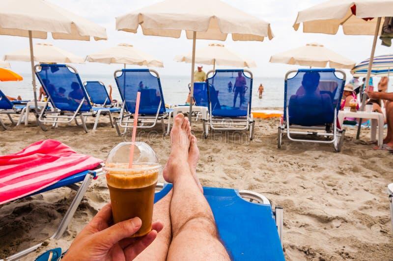 Человек сидя на голубом deckchair с кофе льда в руке на пляже Paralia на побережье Эгейского моря в Греции стоковое фото